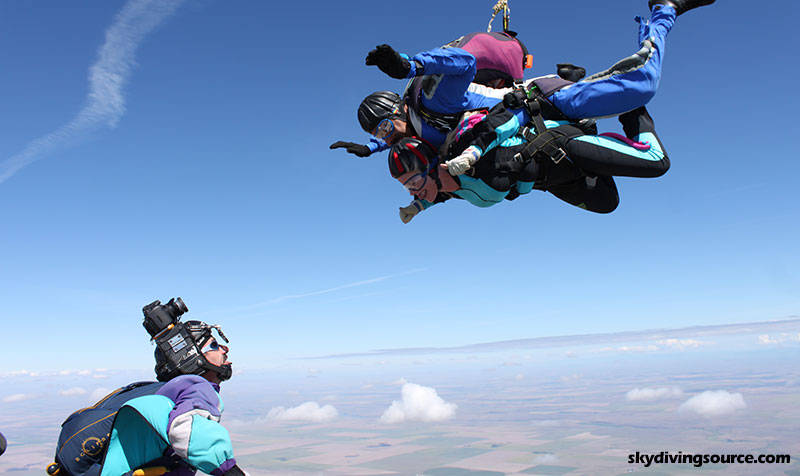 A videographer filming a tandem skydive