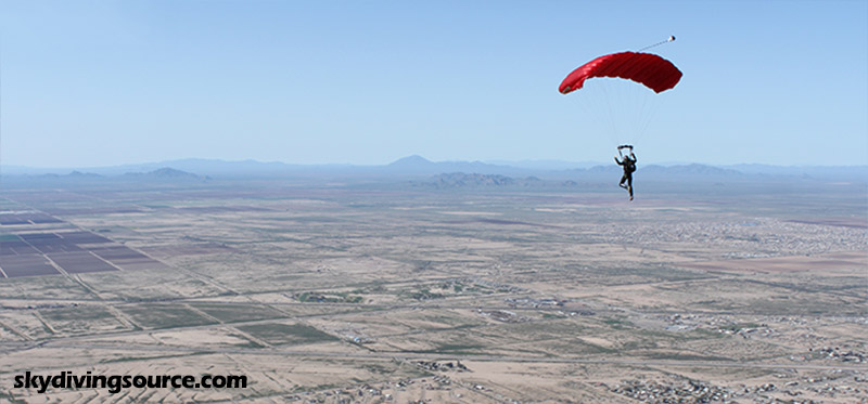Skydiver under a red parachute over Eloy, AZ