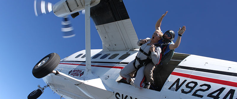 Tandem Skydivers making an exit from an aircraft