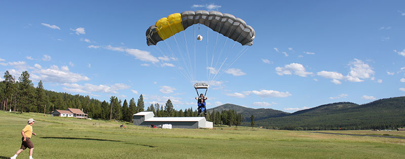 A tandem parachute coming in for landing